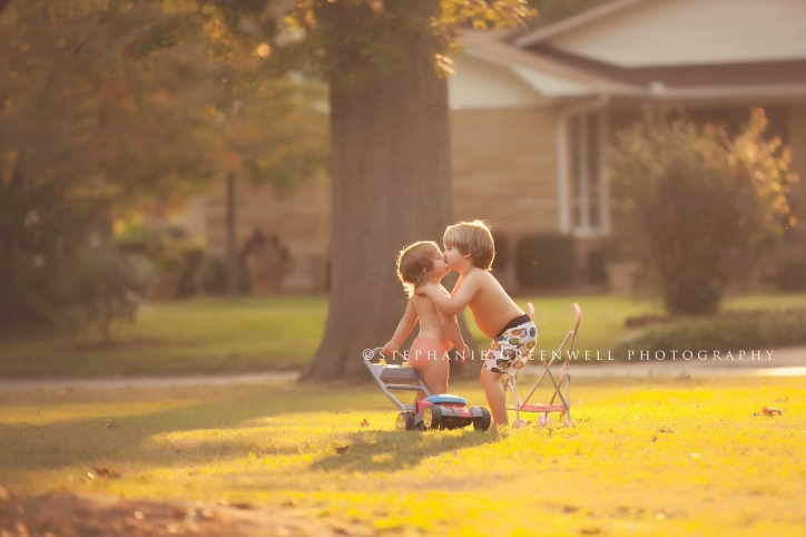 boy kissing girl siblings sunset toy lawn mower stroller southeast missouri photographer stephanie greenwell