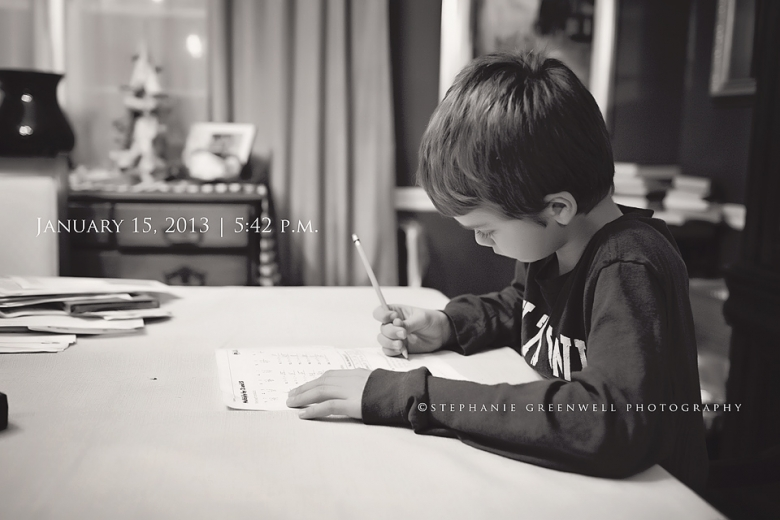 boy doing homework at table holding pencil stephanie greenwell